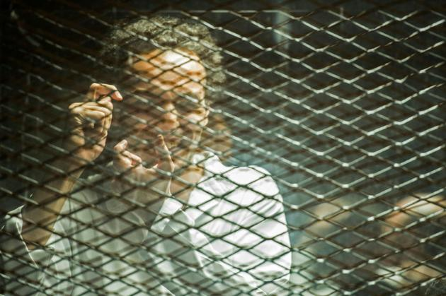 """Le photojournaliste égyptien Mahmoud Abu Zeid """"Shawkan"""" dans le box des accusés dans un tribunal du Caire le 8 septembre 2018 [Mohamed el-Shahed / AFP]"""