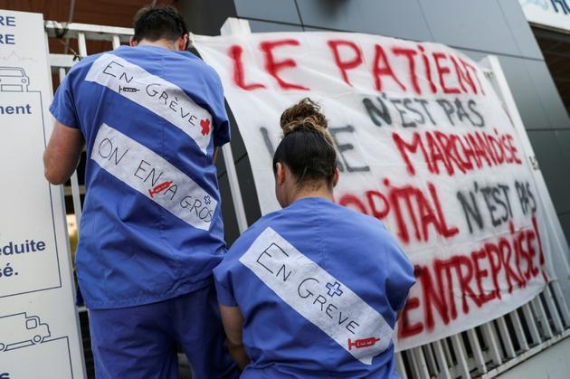 Des soignants des urgences de l'AP-HP attachent des banderoles à l'entrée de La Pitié-Salpêtrière à Paris, le 15 avril 2019, pour protester contre leurs conditions de travail.  [KENZO TRIBOUILLARD / AFP/Archives]