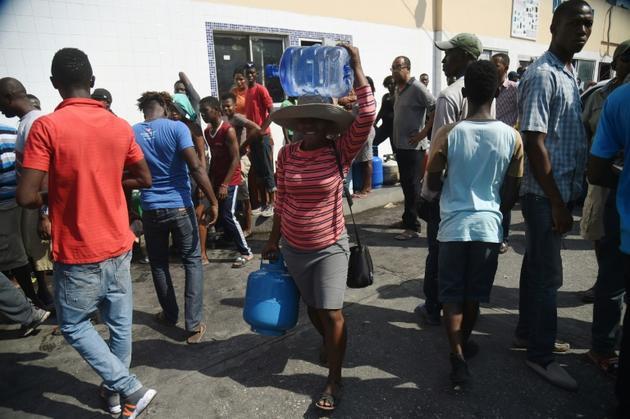 Des habitants de Port-au-Prince font la queue pour des bouteilles de gaz et des bidons d'eau, le 16 février 2019 en Haïti [HECTOR RETAMAL / AFP]