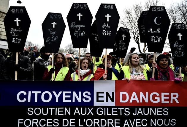 """Des """"gilets jaunes"""" manifestent, samedi 19 janvier 2019 à Paris, avec des pancartes en forme de cercueil évoquant les personnes tuées depuis le début du mouvement en novembre [Philippe LOPEZ / AFP]"""