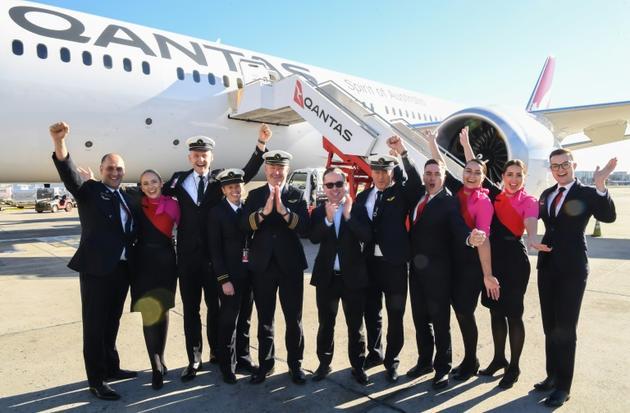 Le PDG de Qantas Alan Joyce (c) entouré des membres de l'équipage du vol le plus long de l'histoire posent devant l'appareil, le 20 octobre 2019 à Sydney [DAVID GRAY / QANTAS/AFP]