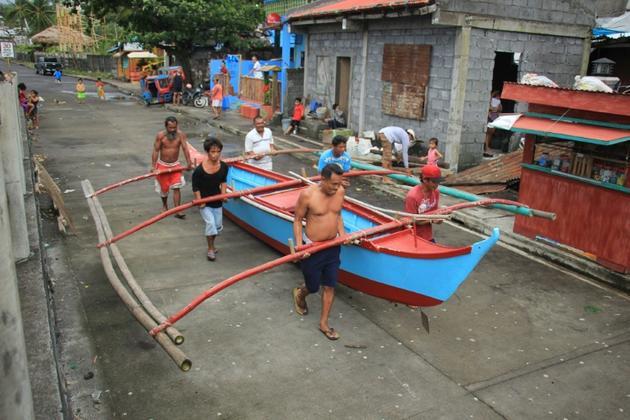 Des habitants de Legaspi City, province d'Albay, au sud de Manille, mettent une embarcation à l'abri avant l'arrivée du typhon Kammuri [RAZVALE SAYAT / AFP]