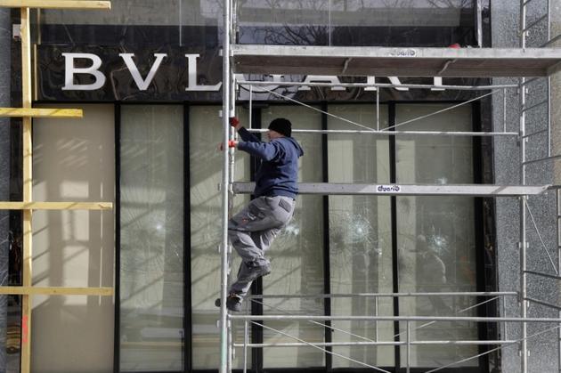 """Installation d'un panneau de bois devant la vitrine brisée d'une boutique sur les Champs-Elysées au lendemain de la manifestation des """"gilets jaunes"""", le 17 mars 2019 à Paris [Geoffroy VAN DER HASSELT / AFP]"""