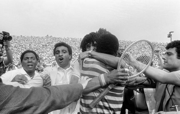 Le Français Yannick Noah embrasse son père camerounais Zaccharie,  le 5 juin 1983, sur le cour central de Roland-Garros à Paris après avoir remporté les 23e Internationaux de France [Dominique Faget / AFP/Archives]