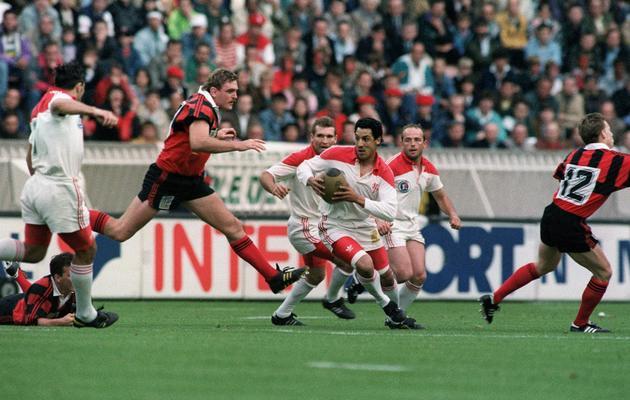 Le capitaine biarrot Serge Blanco (balle en main) face au capitaine toulonnais Eric Melville (G), le 6 juin 1992 lors de la finale du championnat de France au Parc des Princes à Paris [Jean-Loup Gautreau / AFP]