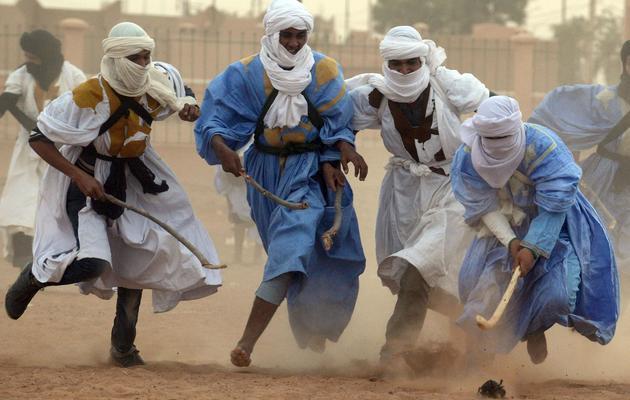 """Des hommes jouent au """"hockey nomade"""" dans le désert marocain, le 16 mars 2013 [Fadel Senna / AFP]"""