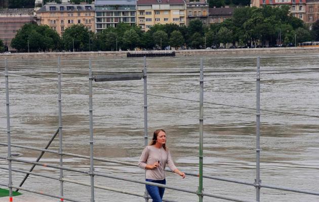 Une jeune femme marche sur une construction métallique du fait de la crue du Danube, le 6 juin 2013 à Budapest [Attila Kisbenedek / AFP]