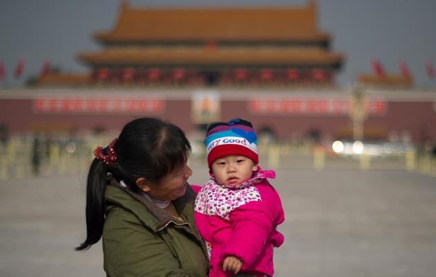 Une femme et son enfant place Tiananmen, le 9 novembre 2012 à Pékin [Ed Jones / AFP]