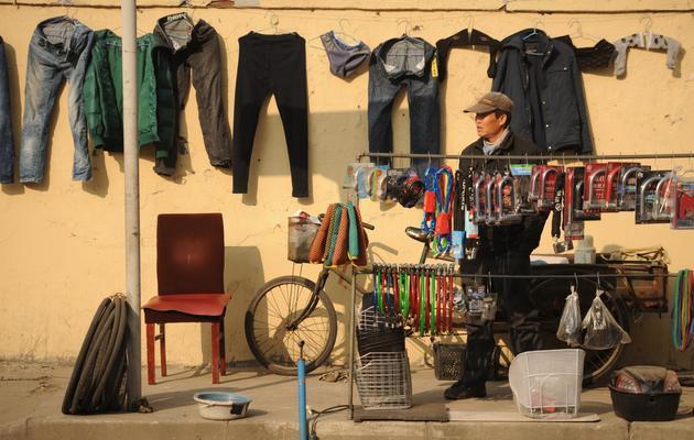 Un réparateur de bicyclette attend les clients, le 10 janvier 2013 à Pékin [Peter Parks / AFP/Archives]