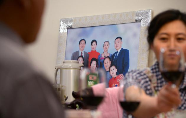 Li Na et Chi Shubo boivent du vin dans leur appartement de la banlieue de Pékin, le 12 mai 2013 [Wang Zhao / AFP/Archives]