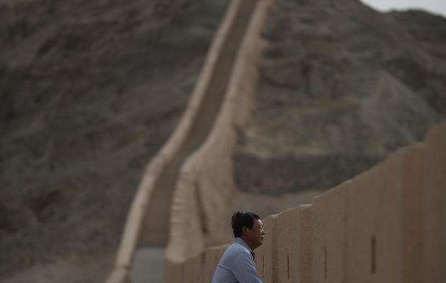 Yang Yongfu regarde l'horizon depuis un pan de la Grande Muraille de Chine qu'il a lui même restauré, le 14 mai 2013 [Ed Jones / AFP]