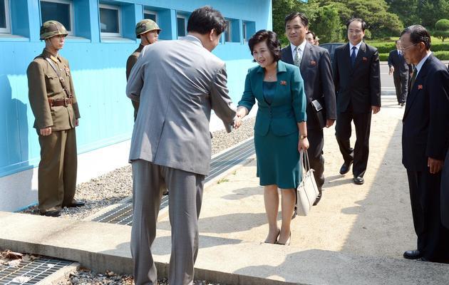La chef de la délégation nord-coréenne Kim Song-Hye (C) est accueillie par un responsable sud-coréen alors qu'elle traverse la frontière à Panmunjom [South Korean Unification Ministry / Ministère sud-coréen de l'unification/AFP]
