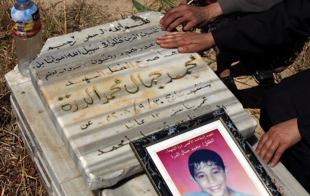 La famille de Mohammad al-Doura se recueille sur sa tombre, au cimetière de Bureij, dans la bande de Gaza, le 20 mai 2013 [Mohammed Abed / AFP]