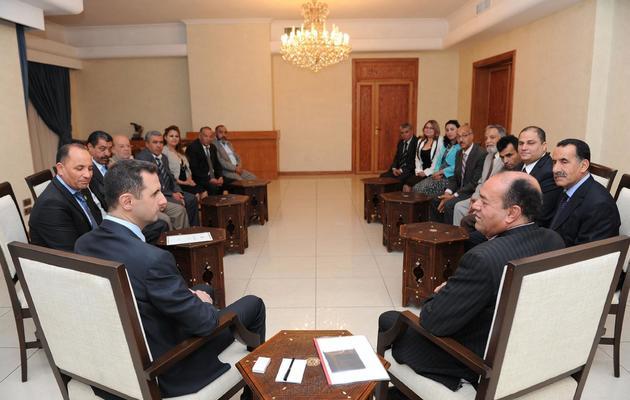 Photo fournie le 23 mai 22013 par l'agence syrienne SANA montrant Bachar al-Assad (G) entouré de dirigeants de partis tunisiens [- / AFP]