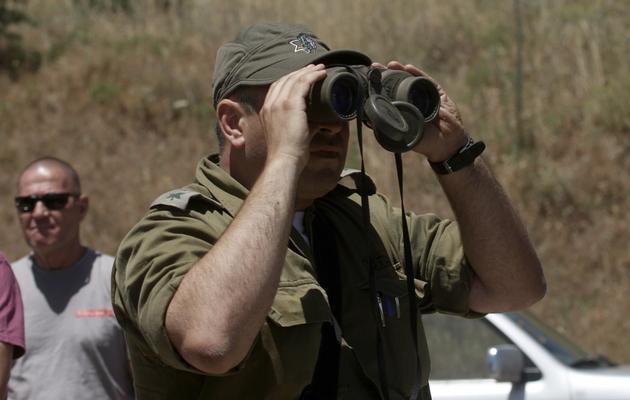 Un officier israélien observe dans le Golan le côté syrien de la frontière près de Qouneitra, le 6 juin 2013 [Jalaa Marey / AFP]