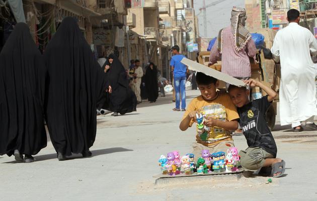 Deux enfants irakiens vendent des jouets sur la route qui mènent au mausolée de l'Imam Ali, à Najaf, en Irak, le 11 juin 2013 [Ali al-Saadi / AFP]