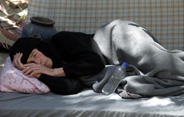Une vieille dame syrienne réfugiée à Arsaal, au Liban, dort allongée sur le sol, le 14 juin 2013 [Joseph Eid / AFP]