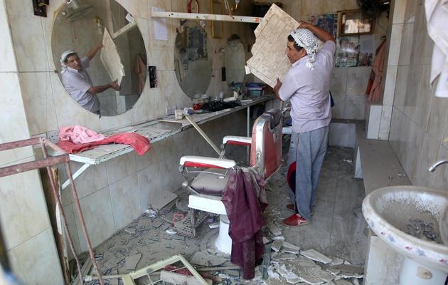 Un homme déblaie son échoppe de barbier après une explosion à Aziziyah, au sud de Bagdad, le 16 juin 2013 [Ahmad al-Rubaye / AFP]
