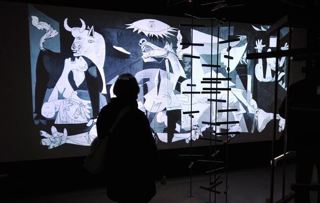 """Une personne regarde, le 5 janvier 2009 au Musée Granet à Aix-en-Provence, une projection interactive du célèbre tableau de Pablo Picasso """"Guernica"""" [Gerard Julien / AFP/Archives]"""