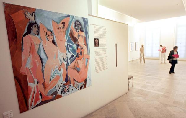 """Des personnes regardent, le 27 septembre 2005 au musée Picasso à Paris, des oeuvres de Picasso, avec en premier plan """"Les Demoiselles d'Avignon"""" [Mehdi Fedouach / AFP/Archives]"""