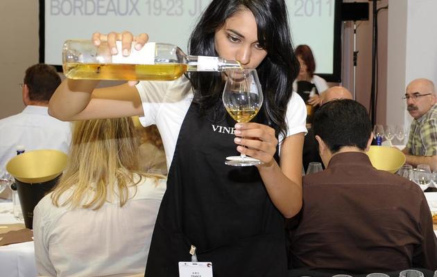 Une femme sert des verres de Sauternes, le 22 juin 2011 à l'occasion du Vinexpo à Bordeaux-Lac [Jean-Pierre Muller / AFP/Archives]