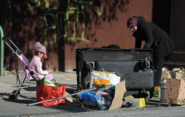 Une femme fouille des poubelles, avec son enfant dans une poussette [Gerard Julien / AFP/Archives]