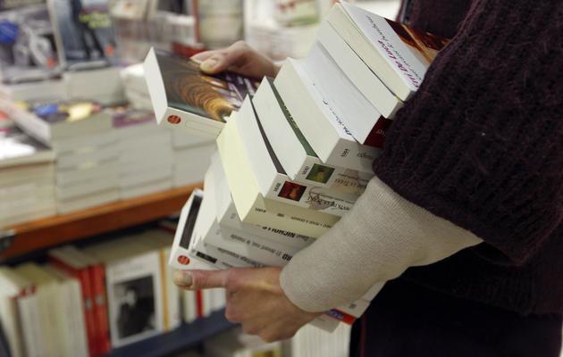 Un eployé d'une librairie porte des livres [Francois Guillot / AFP/Archives]