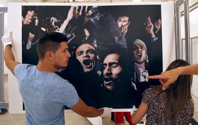 Un homme accroche une photo d'Alex Majoli avant l'ouverture du Visa pour l'Image de Perpignan le 5 septembre 2012 [Raymond Roig / AFP/Archives]
