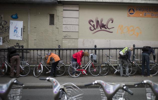 Des cyclistes accrochent leurs vélos à une grille, à Paris le 18 octobre 2012 [Fred Dufour / AFP/Archives]