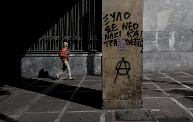 Une femme marche près d'un mur où sont inscrits des messages hostiles aux banques et aux nazis, dans une rue d'Athènes, le 7 novembre 2012 [Panayiotis Tzamaros / AFP/Archives]