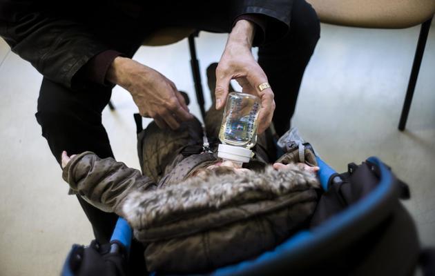 Un adulte donne à boire à un bébé, le 20 février 2013 à Paris [Fred Dufour / AFP/Archives]