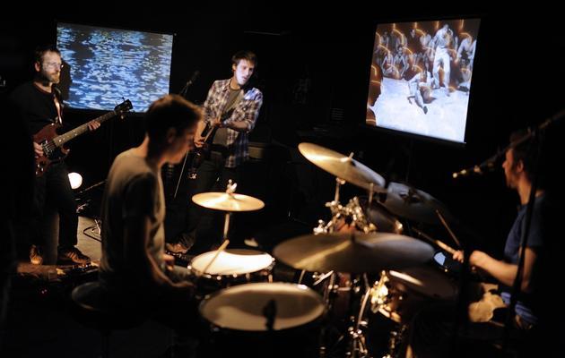 """Des membres du collectif 'Vitrine en cours"""" en concert devant des projections de vieux films à Rennes le 19 avril 2013 [Jean-Sebastien Evrard / AFP]"""