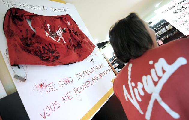 Des salariés de Virgin Megastore Strasbourg exposent, le 18 mai 2013, les produits cassés et abîmés après trois journées de destockage massif [Frederick Florin / AFP/Archives]