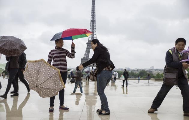 Des touristes s'accrochent à leurs parapluies sur la place du Trocadéro, le 20 mai 2013 [Fred Dufour / AFP]