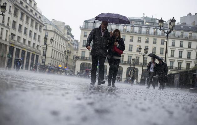 Des gens sous la pluie à Paris [Fred Dufour / AFP]