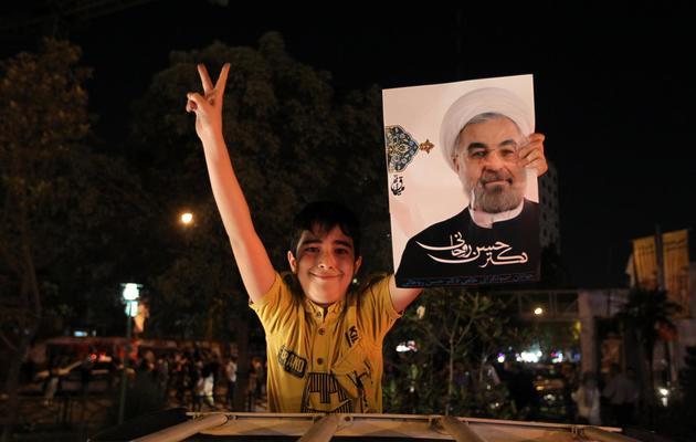 Un jeune supporteur de Hassan Rohani montre un portrait du candidat à l'élection présidentielle iranienne, le 12 juin 2013 à Téhéran [Atta Kenare / AFP]