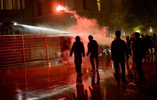 La police suisse repousse des manifestants le 25 mai 2013 à Berne devant le Parlement Fédéral [Fabrice Coffrini / AFP]