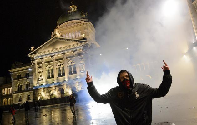 Un manifestant au milieu des gaz lacrymogènes lors des affrontements devant le Parlement Fédéral à Berne, le 25 mai 2013 [Fabrice Coffrini / AFP]