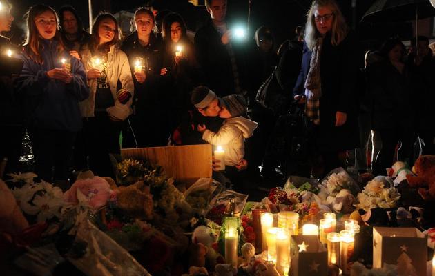 Enfants et adultes se recueillent devant un mémorial improvisé en mémoire des victimes du massacre de l'école primaire Sandy Hook, le 16 décembre 2012 à Newtown [Mario Tama / Getty Images/AFP]