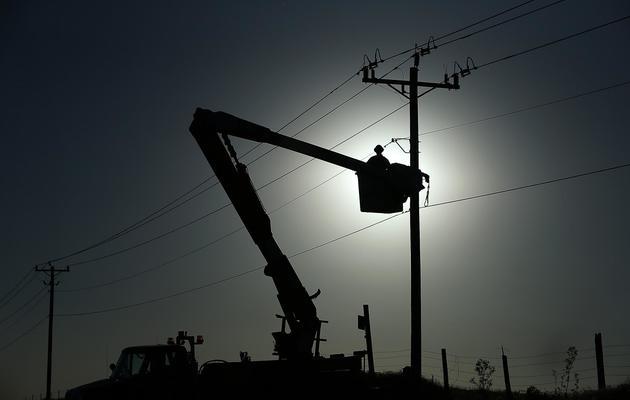 Une personne répare des lignes électriques après le passage d'une tornade à El Reno, dans l'Oklahoma, le 1er juin 2013 [Justin Sullivan / Getty Images/AFP]