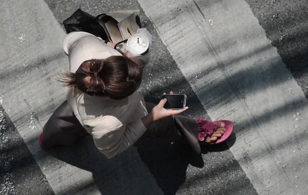 Une femme consulte son smartphone dans la rue [Nicolas Asfouri / AFP/Archives]