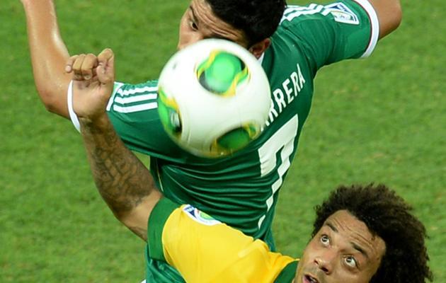Le milieu de terrain mexicain Pablo Barrera  (haut) au duel avec le défenseur brésilien Marcelo lors du deuxième match du groupe A de la Coupe des Confédérations à Fortaleza, le 19 juin 2013 [VANDERLEI ALMEIDA / AFP Photo]