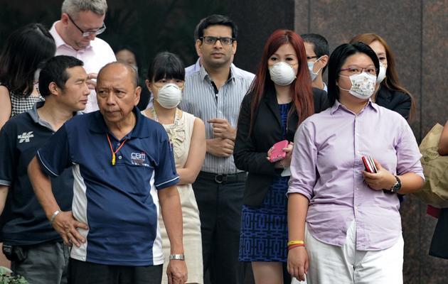 Des personnes portant des masques marchent dans les rues de Singapour, le 20 juin 2013 [ROSLAN RAHMAN / AFP]