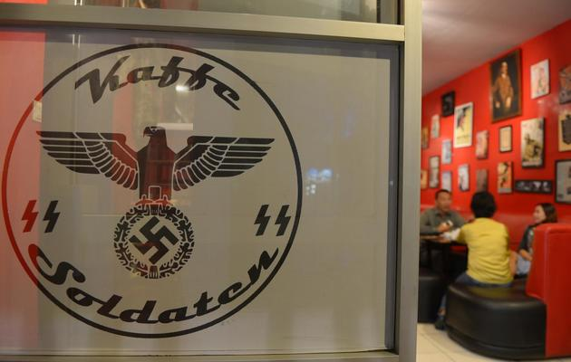 """Des clients dînent à une table du """"Soldaten Kaffee"""", un café d'inspiration nazie, le 16 juillet 2013 à Bandung en Indonésie [Adek Berry / AFP]"""