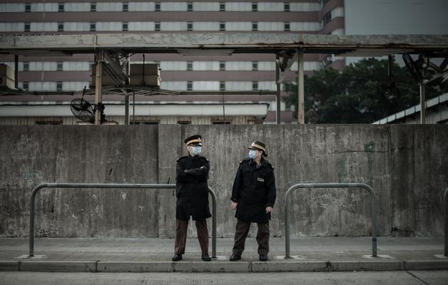 Deux gardes devant le marché aux volailles fermé de Cheung Sha Wan, à Hong Kong, le 28 janvier 2014 [Philippe Lopez / AFP]
