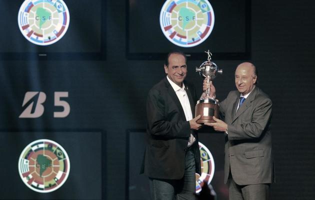 Le président de l'Atletico Mineiro Alexandre Kalil (g) soulève le trophée de la Copa Libertadores remporté par son équipe, lors du tirage au sort de la 55e édition de l'épreuve, le 12 décembre 2013 à Luque au Paraguay [ / AFP/Archives]