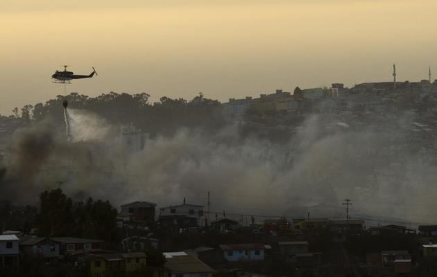 Un hélicoptère combat le 13 avril 2014 le gigantesque incendie qui ravage Valparaiso  [Martin Bernetti / AFP]