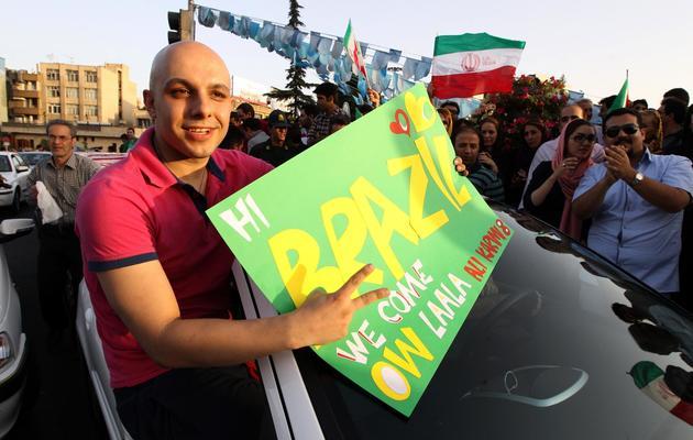 Un Iranien fête la qualification de l'Iran pour le mondial au Brésil le 18 juin 2013 à Téhéran [ATTA KENARE / AFP Photo]