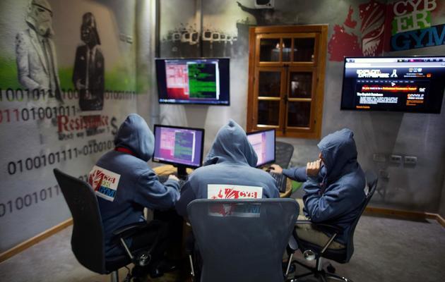 """Trois hackers travaillent devant leur ordinateur dans le centre """"cyber-gym"""" où ils testent la capacité d'employés israéliens à repousser des cyber-attaques, le 30 octobre 2013 près d'Hedera [Menahem Kahana / AFP]"""