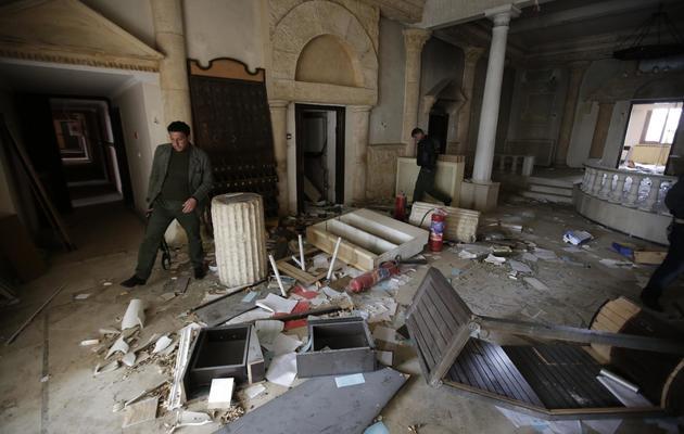 Des policiers syriens inspectent le rez-de-chaussée du Zénobia, hôtel de légende construit dans les années 1920 par une aventurière française sur l'ancien site de Palmyre, qui a été pillé et à moitié brûlé, le 14 mars 2014 [Joseph Eid / AFP]